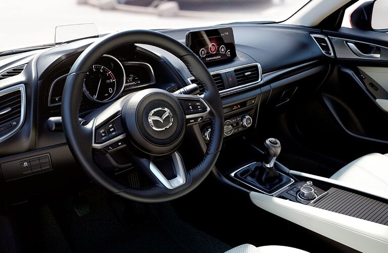 Interior view of the steering wheel and touchscreen inside a 2018 Mazda3