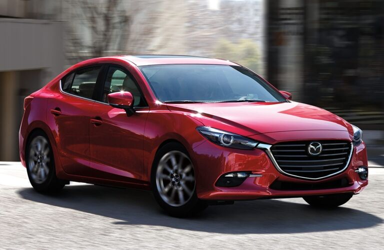 Exterior view of a red 2018 Mazda3 4-Door driving down a city street