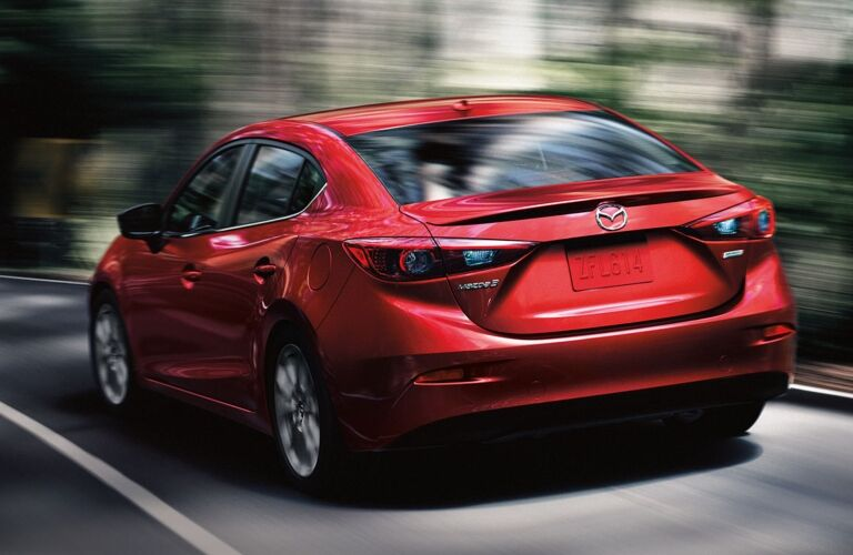 Exterior view of the rear of a red 2018 Mazda3 4-Door driving town a two-lane road