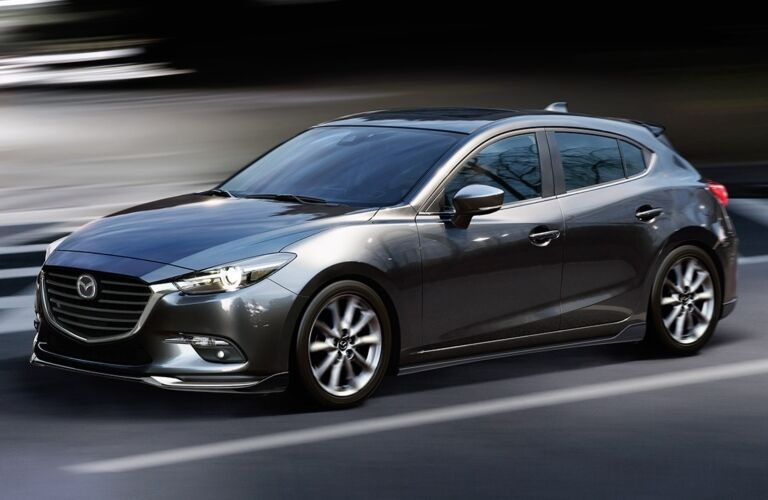 Exterior view of a silver 2018 Mazda3 5-Door driving down a two-lane road