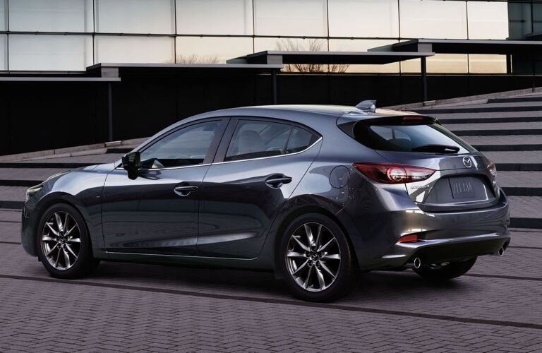 Exterior view of the rear of a 2018 Mazda3 5-Door parked outside an office building