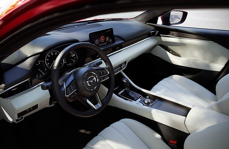 Interior view of the steering wheel and tan seating inside a 2018 Mazda6