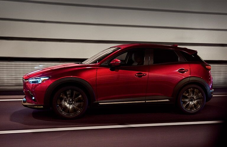 Exterior view of a red 2019 Mazda CX-3 driving through a city tunnel