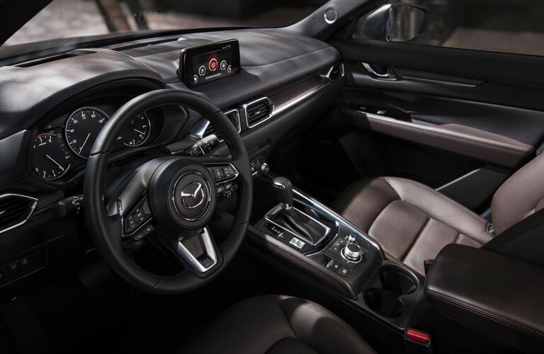 Interior view of the black steering wheel and touchscreen inside a 2019 Mazda CX-5