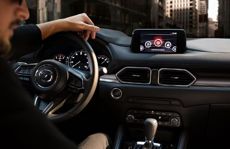 Interior view of the steering wheel and touchscreen inside a 2019 Mazda CX-5 Signature Diesel