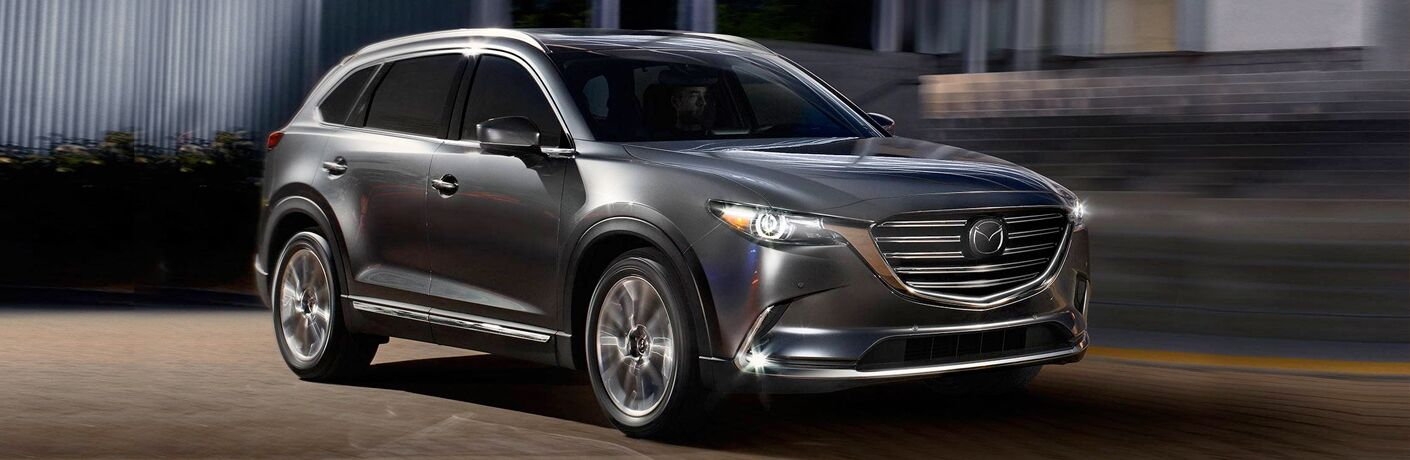 Exterior view of a dark gray 2019 Mazda CX-9 driving down a city street at night