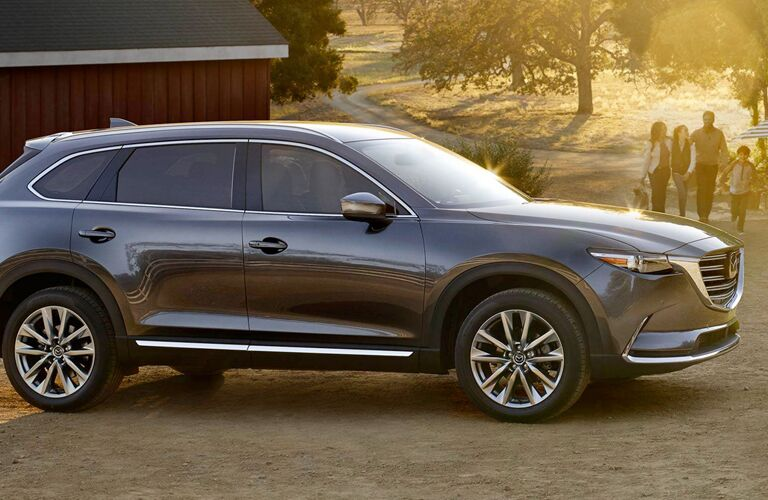 Exterior view of a gray 2019 Mazda CX-9 parked outside a wood building with a family of four approaching the vehicle