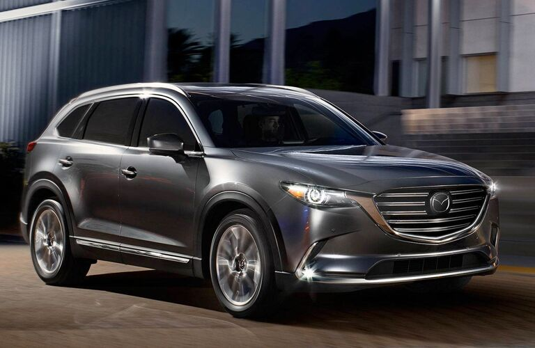 Exterior view of a gray 2019 Mazda CX-9 driving down a city street at night