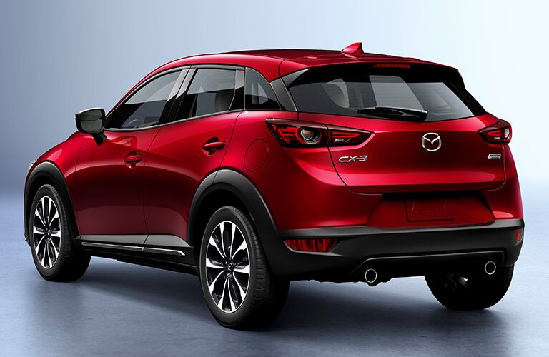 Exterior view of the rear of a red 2018 Mazda CX-3 parked in a gray showroom