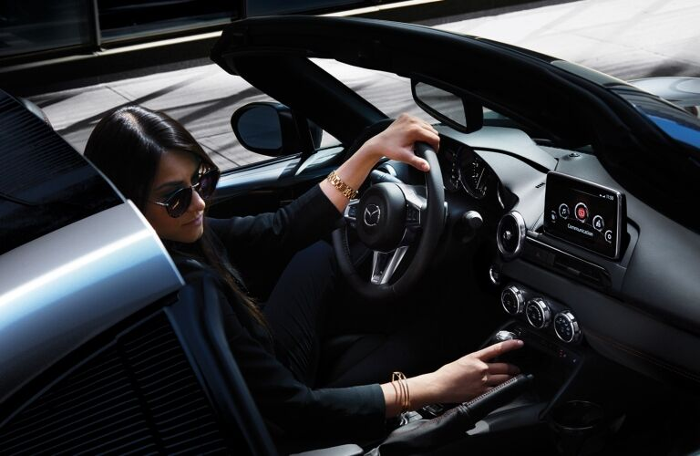 Interior view of a woman siting inside a 2019 Mazda MX-5 Miata RF with one hand on the steering wheel and one hand on the gear stick