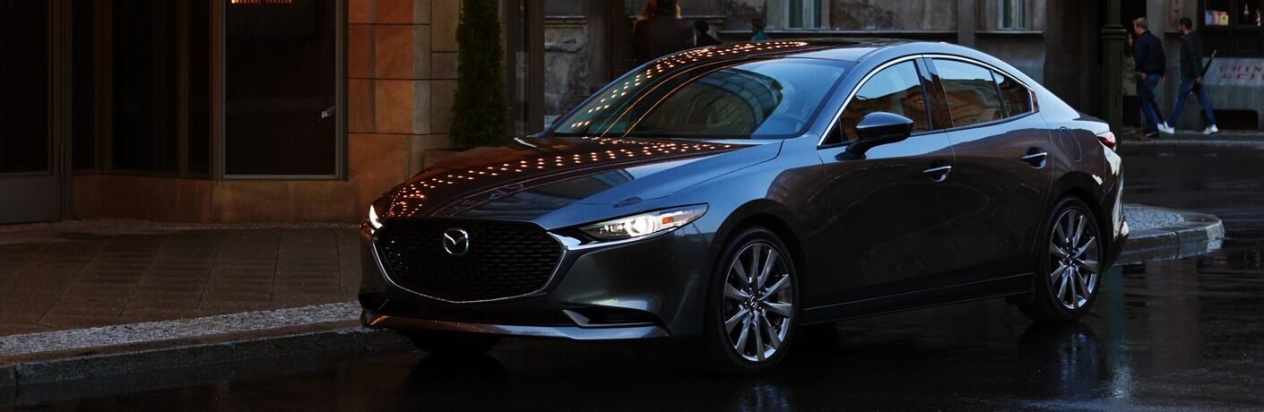 Exterior view of a gray 2019 Mazda3 Sedan parked on a city street