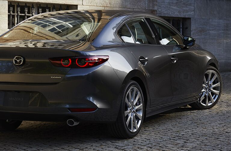 Exterior view of the rear of a gray 2019 Mazda3 Sedan parked outside a building
