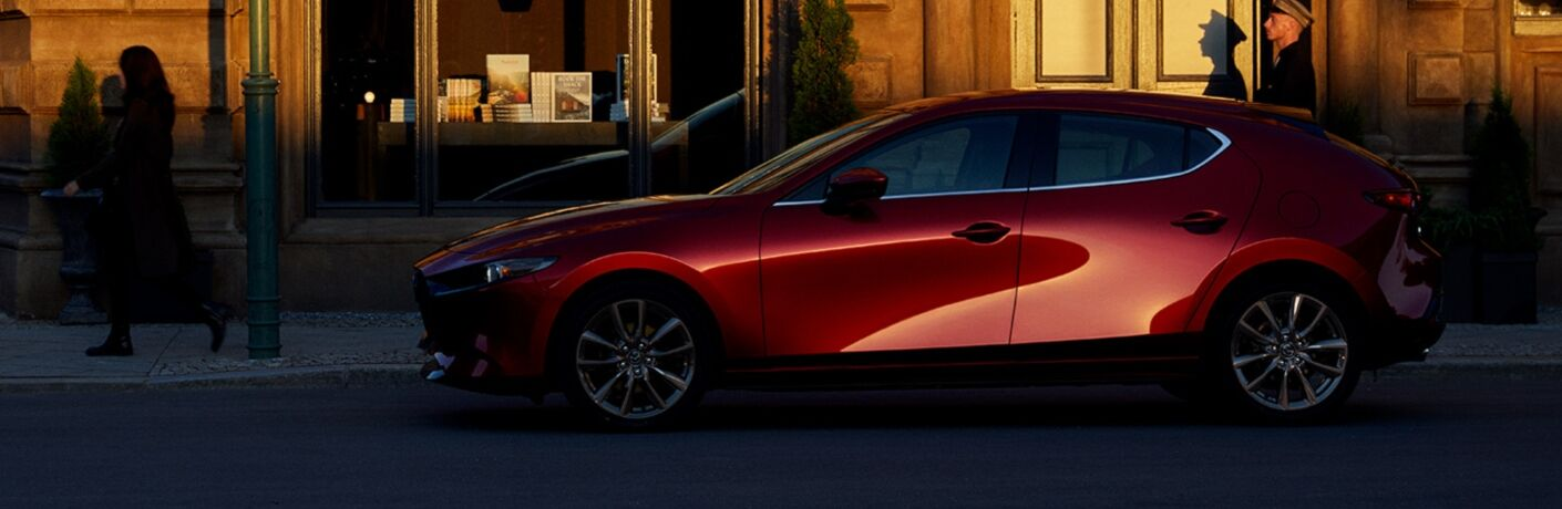 Exterior view of a red 2019 Mazda3 Hatchback parked on a city street