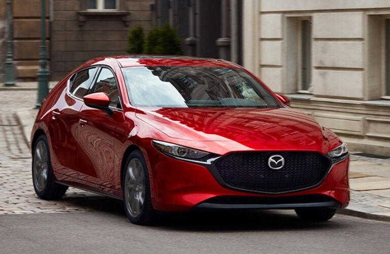Exterior view of a red 2019 Mazda3 Hatchback driving down a city street