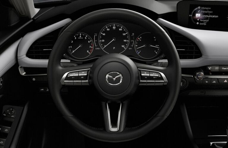 Interior closeup view of the steering wheel and dashboard inside a 2019 Mazda3 Hatchback