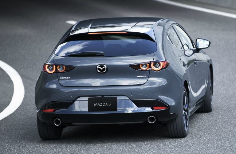 Exterior view of the rear of a gray 2019 Mazda3 Hatchback driving down a road