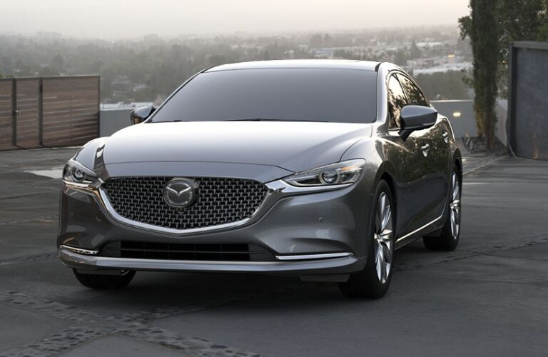 Exterior view of the front of a gray 2019 Mazda6 parked in a long driveway
