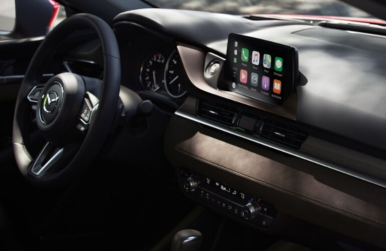 Interior view of the steering wheel and touchscreen with Apple CarPlay inside a 2019 Mazda6