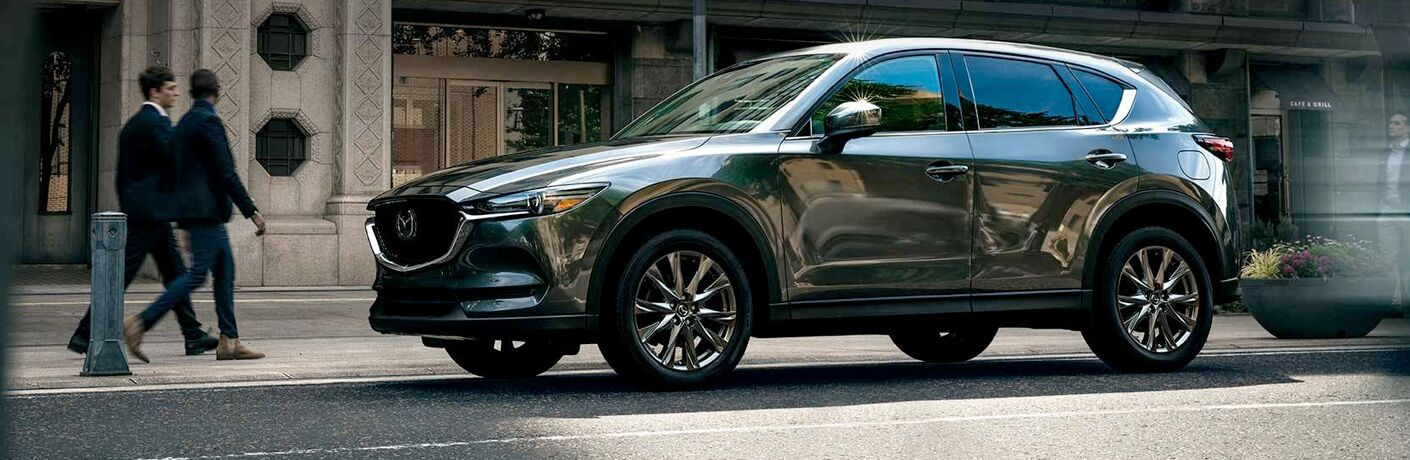 Exterior view of a gray 2019 Mazda CX-5 parked outside an office building in the city