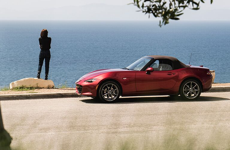 Exterior view of a red 2019 Mazda MX-5 Miata parked near a large body of water