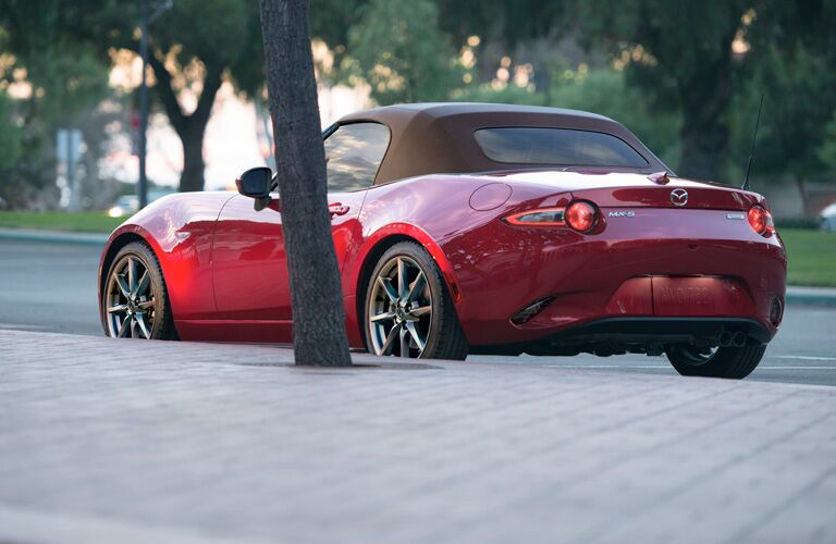 Exterior view of the rear of a red 2019 Mazda MX-5 Miata parked on a suburban street