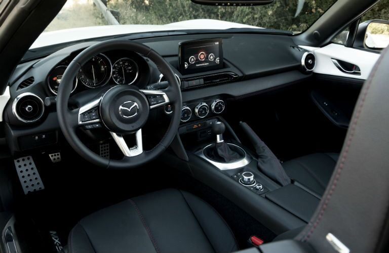 Interior view of the black seating, steering wheel, and touchscreen of a 2019 Mazda MX-5 Miata