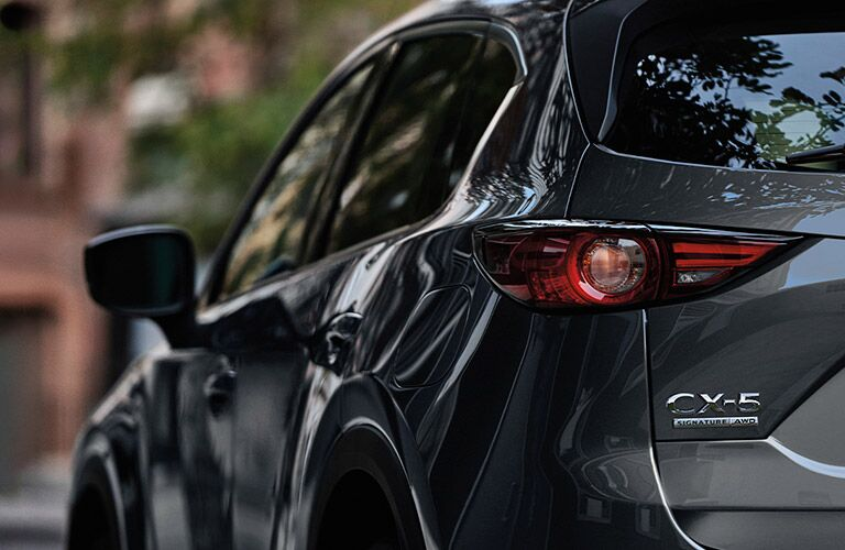 2020 Mazda CX-5 grey paint shot from behind close up on back bumper and driver side brake light with glancing view of driver side doors