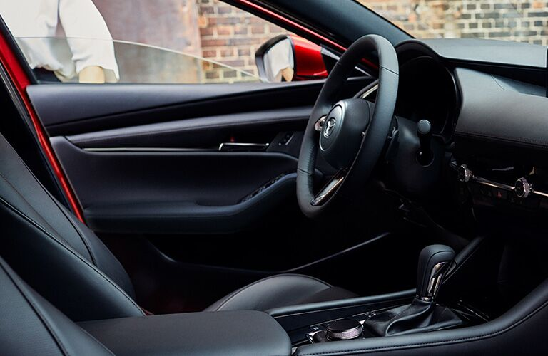 2020 Mazda3 Hatchback interior shot low through passenger window showing steering wheel and seats