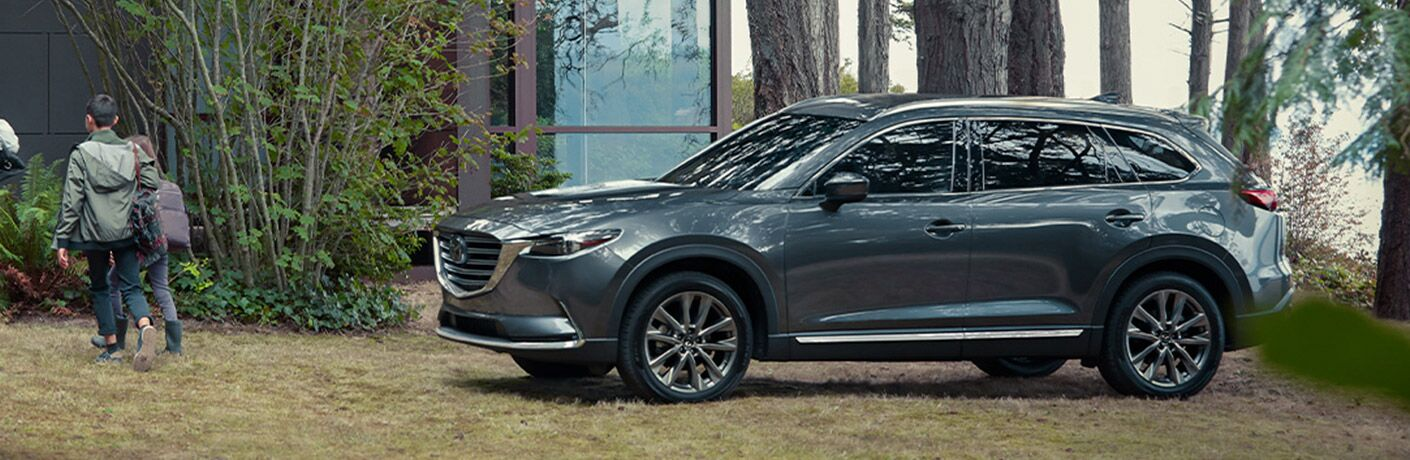 The front and side view of a gray 2020 Mazda CX-9 parked near a house in the forest.