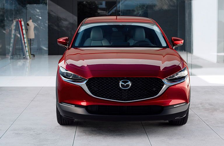 The front view of a red 2020 Mazda CX-30 parked indoors.