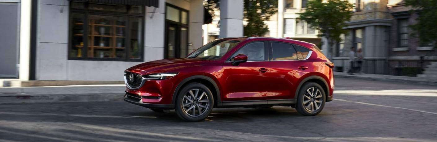 red mazda cx5 driving in city
