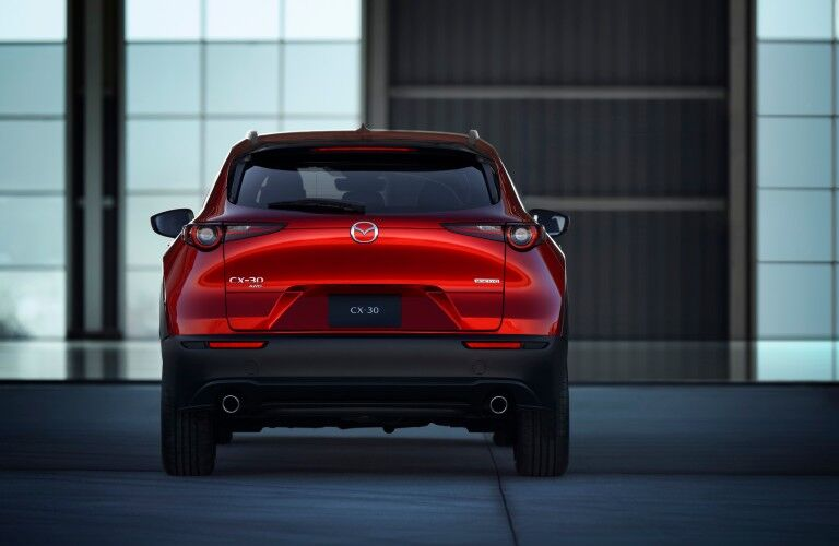 The rear side of a red 2020 Mazda CX-30 parked in an indoor space.