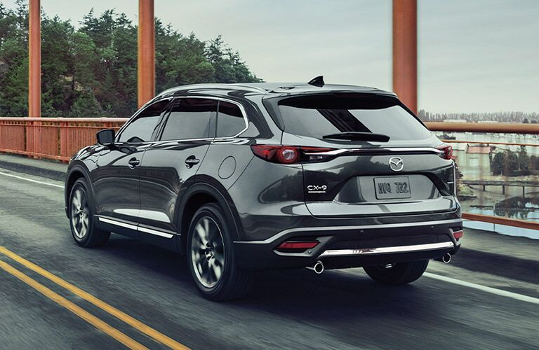 The rear and side view of a gray 2020 Mazda CX-9 driving on a bridge.