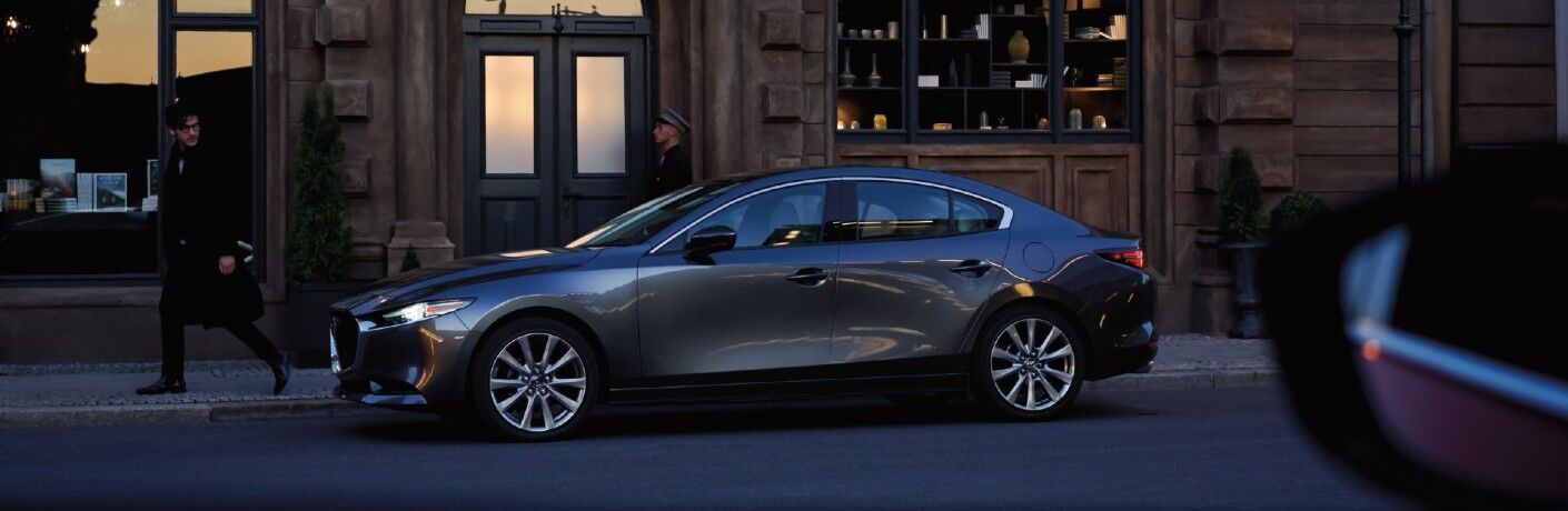 The side view of a dark gray 2021 Mazda3 Sedan parked on a street.
