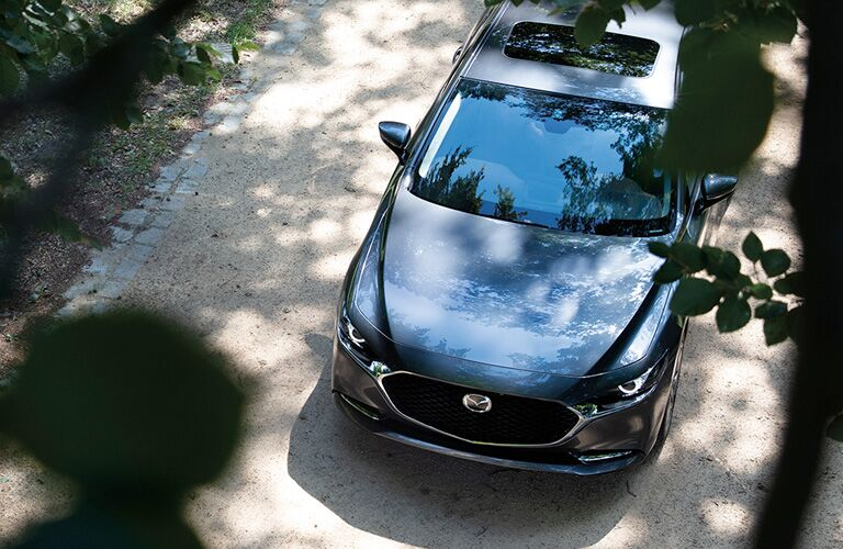 The top view of a gray 2021 Mazda3 Sedan under the trees.