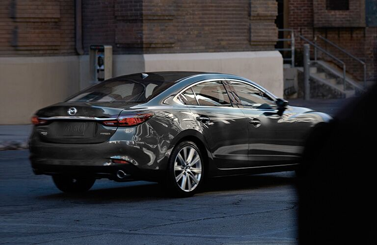 A rear and side view of a gray 2021 Mazda6.
