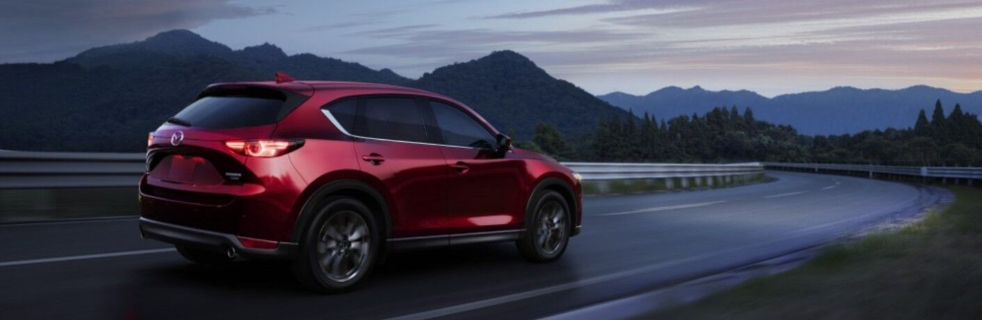 The side view of a red 2021 Mazda CX-5 driving down an open road at dusk.