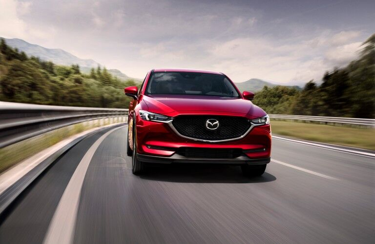 The front image of a red 2021 Mazda CX-5 driving down a road.