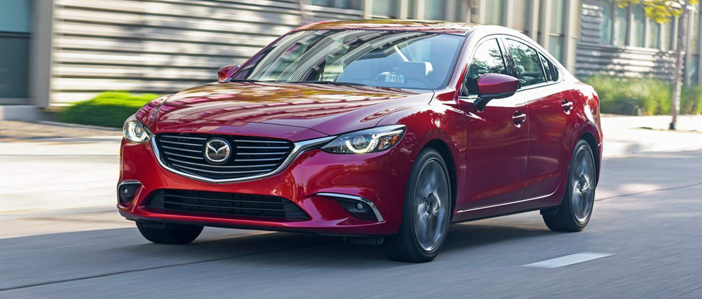 red 2017 mazda mazda6 driving through city street during day