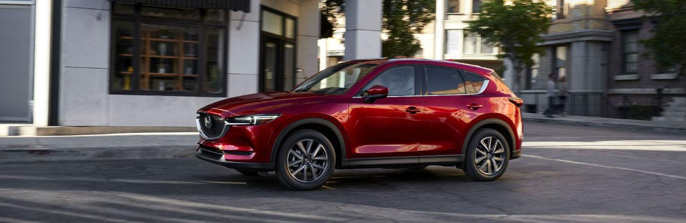 Side View of Red 2017 Mazda CX-5 Driving by Some Buildings