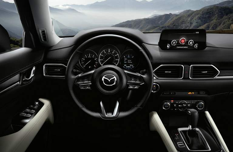 front interior of 2018 mazda cx-5 including steering wheel, dashboard and infotainment system