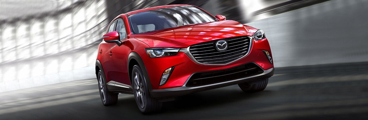 front view of red 2018 mazda cx-3 driving against white background
