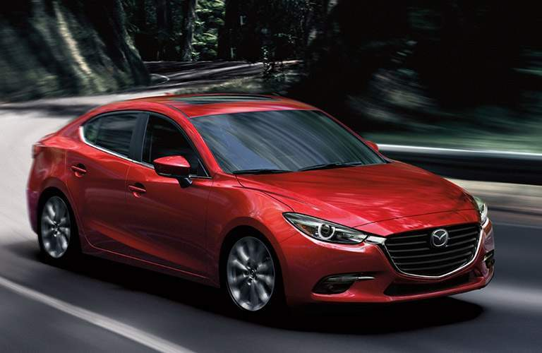 Front View of Red 2018 Mazda3 Sedan Driving Through a Forest