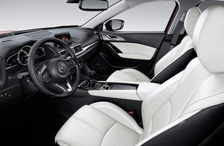 front interior of 2018 mazda mazda3 including steering wheel and infotainment system