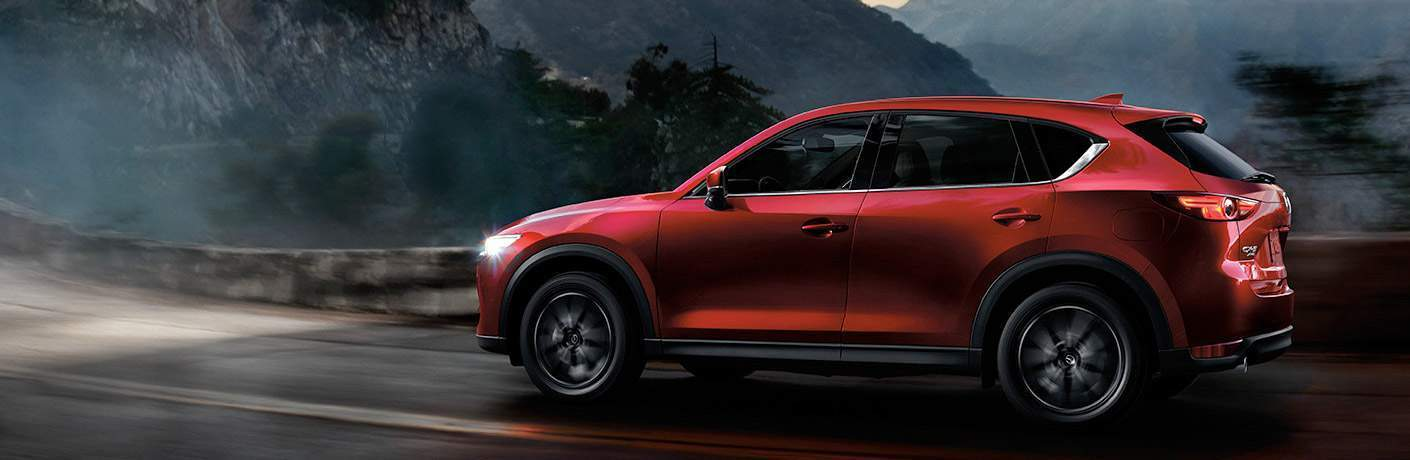 red 2018 mazda cx-5 driving at night with mountains behind it