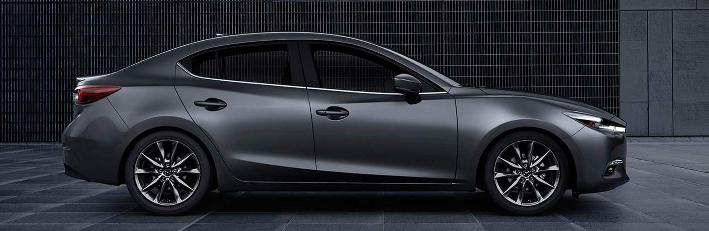 Side View of 2018 Mazda3 Sedan next to a Grey Wall