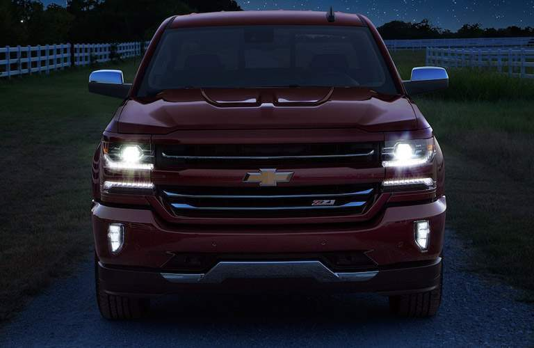 front view of the 2018 Chevy Silverado 1500 driving at night down a farm road