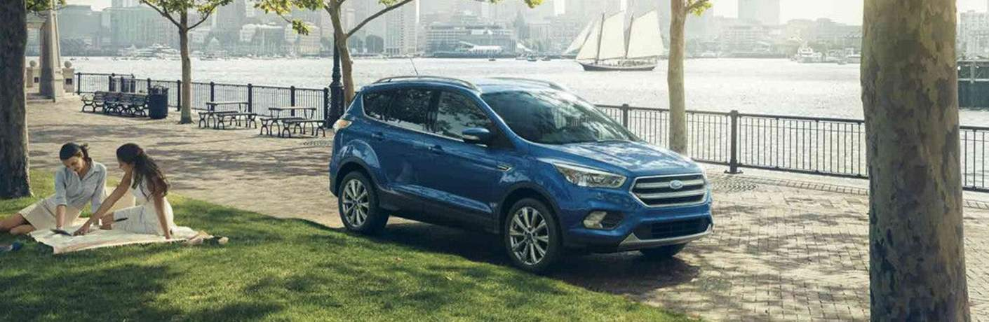Blue 2018 Ford Escape parked on tree lined parkway in front of water
