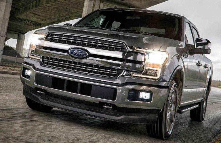 2018 ford f-150 in gray color on rainy road driving with headlights on front grille and fascia visible
