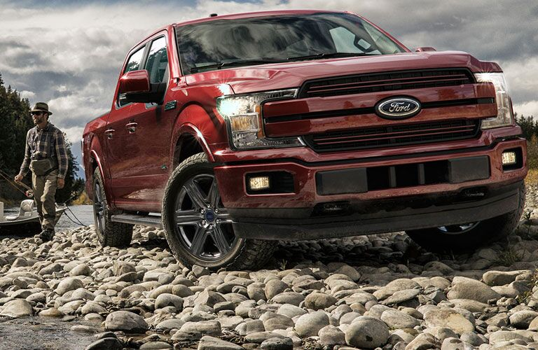 front view of a red 2018 Ford F-150 parked on rocks by a man with a boat